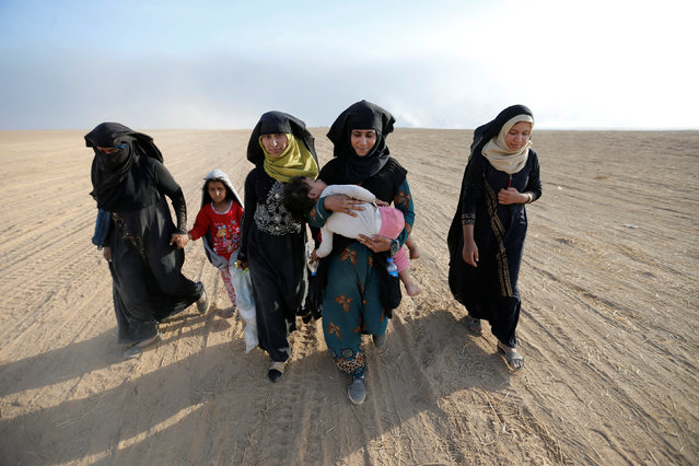 Civilians return to their village after it was liberated from Islamic State militants, south of Mosul, Iraq October 21, 2016. (Photo by Thaier Al-Sudaini/Reuters)