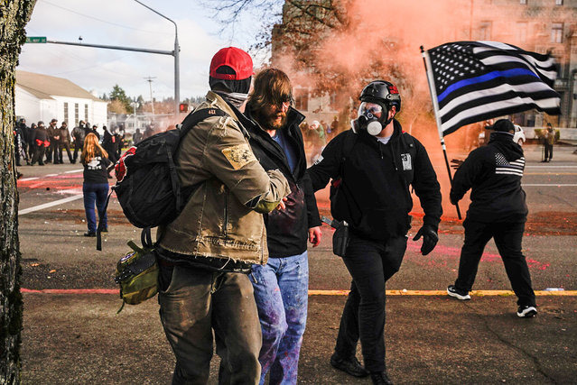 Demonstrators aid a Trump supporter who was beaten by counter-protesters during political clashes on December 12, 2020 in Olympia, Washington. Far-right and far-left groups squared off near the Washington State Capitol following violent clashes over the previous weekend. (Photo by David Ryder/Getty Images)