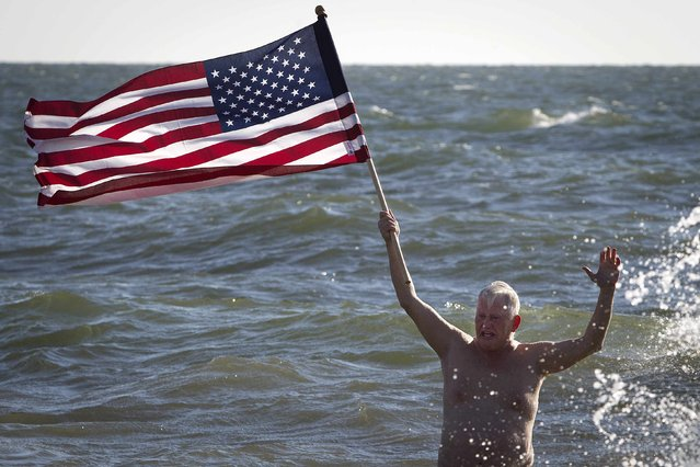 A man holds a U.S. flag while taking part in the Polar Bear Plunge on Coney Island in the Brooklyn borough of New York January 1, 2015. (Photo by Carlo Allegri/Reuters)