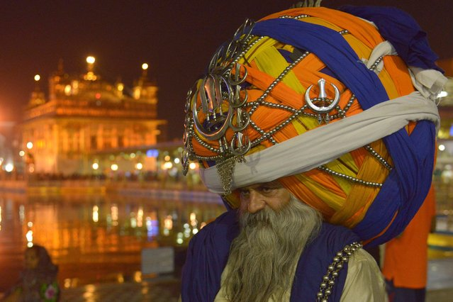 An Indian Sikh Nihang (a traditional Sikh religious warrior) Baba 'Avtar' Singh wears an oversized giant traditional turban as he pay respects at the Golden temple in Amritsar on November 10, 2015 on the eve of the Indian festival of Diwali, the festival of lights. (Photo by Narinder Nanu/AFP Photo)
