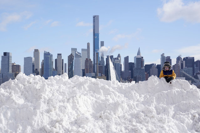 A boy plays on a mound of snow in front of the skyline of New York City in West New York, N.J., Thursday, December 17, 2020. The first major snowstorm of the season left the Northeast blanketed in snow, setting records in some areas. (Photo by Seth Wenig/AP Photo)