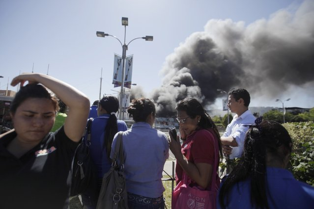 Employees of a Las Cascadas shopping mall evacuate after a fire broke out inside, in Antiguo Cuscatlan January 3, 2015. The fire partially destroyed the Las Cascadas shopping mall and 12 people were treated for smoke inhalation. According to local media, firefighters, emergency personnel and policemen worked to control the fire for three hours. (Photo by Jose Cabezas/Reuters)