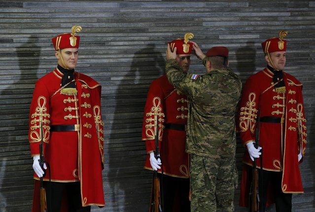 A Croatian soldier adjusts the hat on a member of the guard of honour ahead of  Brdo-Brijuni Process Leaders' Meeting at Presidental office in Zagreb, Croatia, November 25, 2015. (Photo by Antonio Bronic/Reuters)