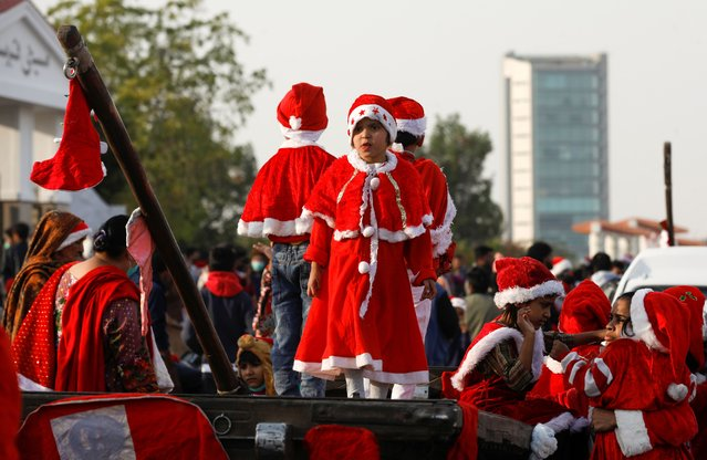 A girl along with others dressed in Santa Claus costumes attends a peace rally ahead of Christmas celebrations in Karachi, Pakistan, December 20, 2020. (Photo by Akhtar Soomro/Reuters)