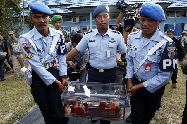 Military policemen carry the flight data recorder of AirAsia QZ8501 to an awaiting military plane for transport back to Jakarta, at the airbase in Pangkalan Bun, Central Kalimantan January 12, 2015. (Photo by Darren Whiteside/Reuters)