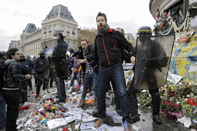 A man is detained by policemen on the candles and flowers set in memory of the victims of the Paris attacks during a protest ahead of the 2015 Paris Climate Conference at the place de la Republique, in Paris, Sunday, November 29, 2015. (Photo by Laurent Cipriani/AP Photo)