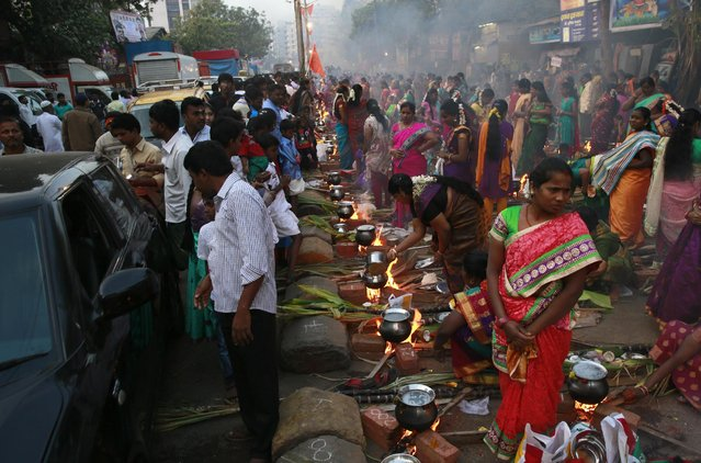 Indian Tamil Hindu women cook special food to celebrate the harvest festival of Pongal on a road at Dharavi, one of the world's largest slums, in Mumbai, India, Thursday, January 15, 2015. This celebration, held according to the solar calendar, marks the beginning of the sun's northward movement, considered to be auspicious. (Photo by Rafiq Maqbool/AP Photo)