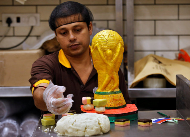 A worker makes a replica of FIFA World Cup 2018 trophy made from sweets at a confectionery workshop in Kolkata, ahead of the FIFA World Cup, in Kolkata, India June 12, 2018. (Photo by Rupak De Chowdhuri/Reuters)