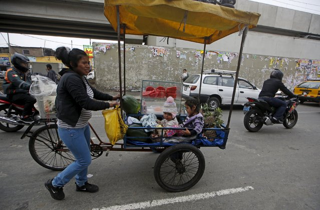 A woman sells fruits while children sit in a tricycle cart in downtown Lima, Peru December 1, 2015. (Photo by Mariana Bazo/Reuters)