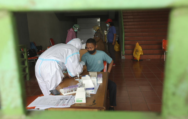 A health worker takes a blood sample from a man for a coronavirus rapid test at the Patriot Candrabhaga Stadium in Bekasi, Indonesia, Monday, January 25, 2021. Indonesia has reported more cases of the virus than any other countries in Southeast Asia. (Photo by Achmad Ibrahim/AP Photo)