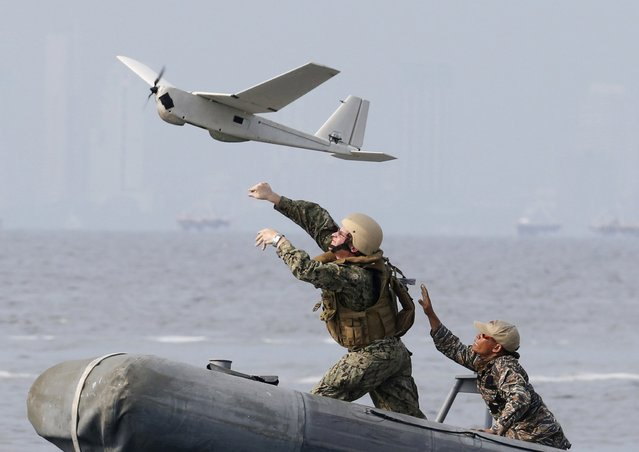 """U.S. (L) and Philippine Navy servicemen launch an Unmanned Aerial Vehicle (UAV) aboard a patrol boat during a joint annual military exercise called """"Carat"""" at the former U.S. military base Sangley Point in Cavite city, west of Manila, on June 28, 2013. (Photo by Erik De Castro/Reuters)"""