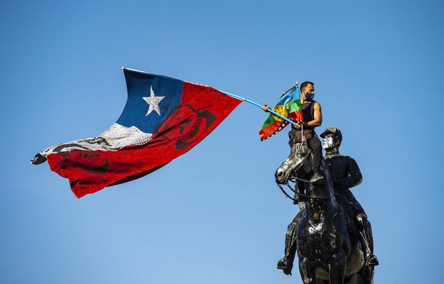 A demonstrator flutters a Chilean and a Mapuche indigenous flags from the top of the General Baquedano monument in Plaza Italia square during a protest against Chilean President Sebastian Pinera's government in Santiago on October 09, 2020. (Photo by Martin Bernetti/AFP Photo)