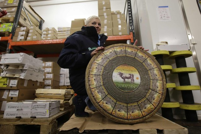 Sophie Desailly, fourth generation of cheese vendors, poses with a wheel of Comte cheese at Rungis International food market as buyers prepare for the Christmas holiday season in Rungis, south of Paris, December 11, 2015. (Photo by Philippe Wojazer/Reuters)