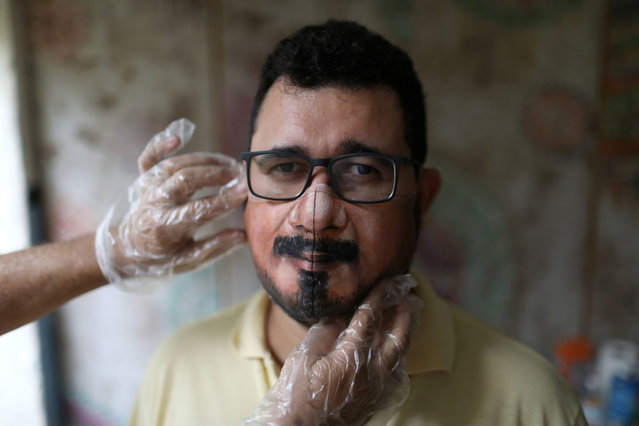 Wescley Menezes receives help from plastic artist Jorge Silva Roriz to adjust his customized protective mask, amid the outbreak of the coronavirus disease (COVID-19), in Rio de Janeiro, Brazil on November 10, 2020. (Photo by Pilar Olivares/Reuters)