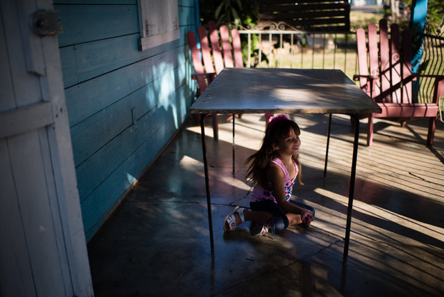 After all the guests have left her fourth birthday party, Belinda Gutierrez sits under the table that held her birthday cake on March 30, 2015. Her family recently moved to Camilo Cienfuegos in 2012 from Havana to have more space and a more peaceful life. Belinda has her own room which is filled with toys and clothes. The family lives in one of the original wooden homes built by the Hershey Company for the workers. Her father is a manager at The Havana Club rum distillery in nearby Santa Cruz del Norte. (Photo by Sarah L. Voisin/The Washington Post)