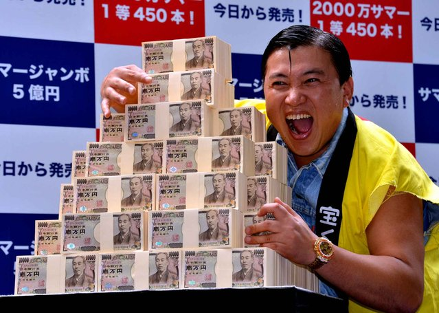 Japanese comic Sugichan poses with 500 million yen (3.9 million euros) for the giant lottery was in Tokyo on July 10, 2013. Thousands of people have been queuing for tickets in the hope of becoming a millionaire. (Photo by Yoshikazu Tsuno/AFP Photo)
