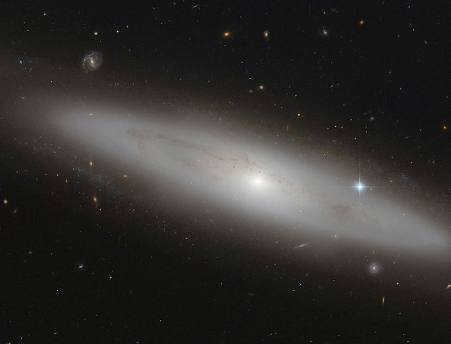 NGC 4866, a lenticular galaxy, is shown in this NASA handout. Situated about 80 million light-years from earth, this image was captured by the Advanced Camera for Surveys, an instrument on the NASA/ESA Hubble Space Telescope. (Photo by Reuters/European Space Agency/NASA/ESA Hubble Space Telescope)