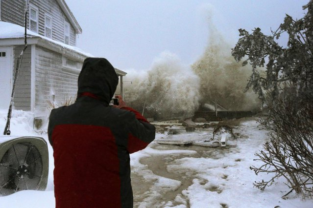 Waves crash against an ocean front house after causing a break in the sea wall during a winter blizzard in Marshfield, Massachusetts January 27, 2015. (Photo by Brian Snyder/Reuters)