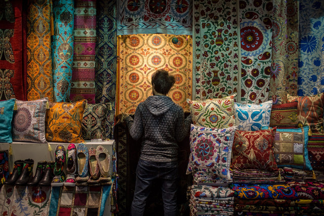 A man works at a rug shop at the Grand Bazaar on December 18, 2015 in Istanbul, Turkey. Despite the expected growth in western and luxury brands, handmade, traditional and turkish made products continue to be popular amongst local communities. The cheap price and convenience of local neighborhood stores and markets continues to grow. (Photo by Chris McGrath/Getty Images)