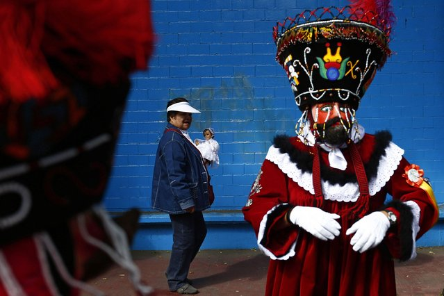A Chinelo (R) costumed dancer stands nearby as a woman walks past with a dressed-up doll representing the baby Jesus, during a celebration to mark 40 days after the birth of Jesus, in Xochimilco on the outskirts of Mexico City, February 2, 2015. (Photo by Edgard Garrido/Reuters)