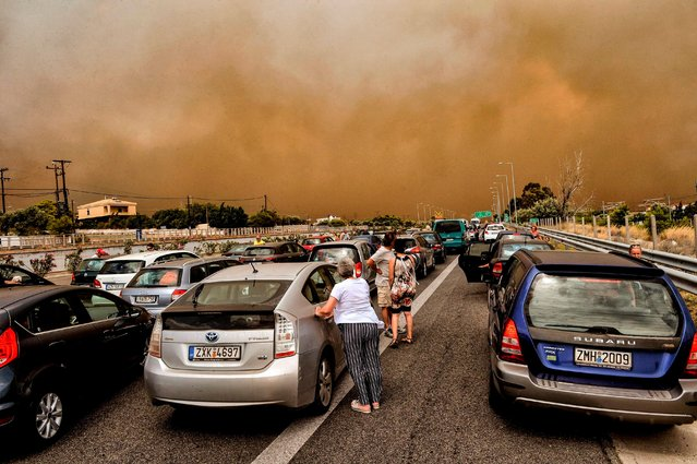 "Cars are blocked at the closed National Road during a wildfire in Kineta, near Athens, on July 23, 2018. More than 300 firefighters, five aircraft and two helicopters have been mobilised to tackle the ""extremely difficult"" situation due to strong gusts of wind, Athens fire chief Achille Tzouvaras said. (Photo by Valerie Gache/AFP Photo)"