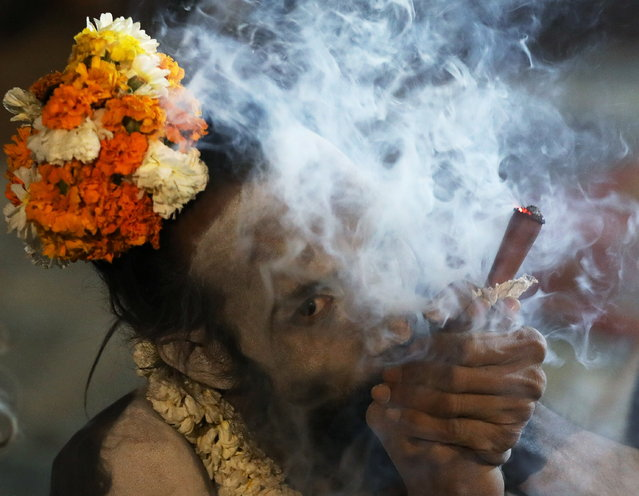 """A Sadhu or Hindu holy man smokes outside his tent ahead of the the first Shahi Snan at """"Kumbh Mela"""" or the Pitcher Festival, in Haridwar, India, March 11, 2021. (Photo by Anushree Fadnavis/Reuters)"""
