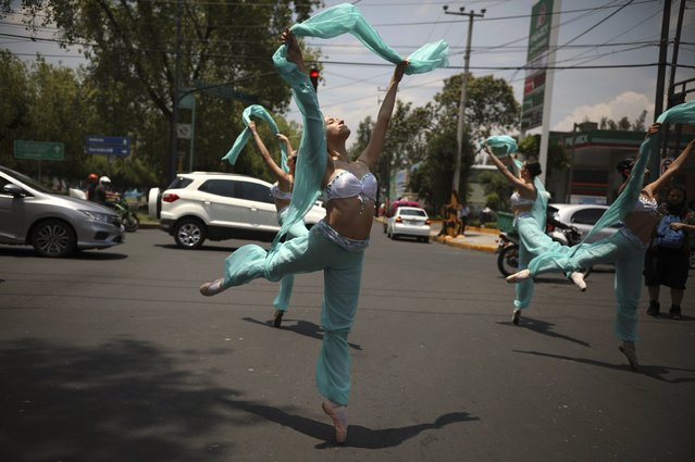 Ballerinas dance in the middle of a street during a red traffic light in Mexico City, Saturday, July 28, 2018. In this sprawling megalopolis notorious for its clogged streets, a theater company sent out tutu-clad dancers out to delight motorists at snarled intersections with snippets from ballet classics like The Nutcracker and Swan Lake all in the 58 seconds it takes for the light to go from red to green. (Photo by Emilio Espejel/AP Photo)
