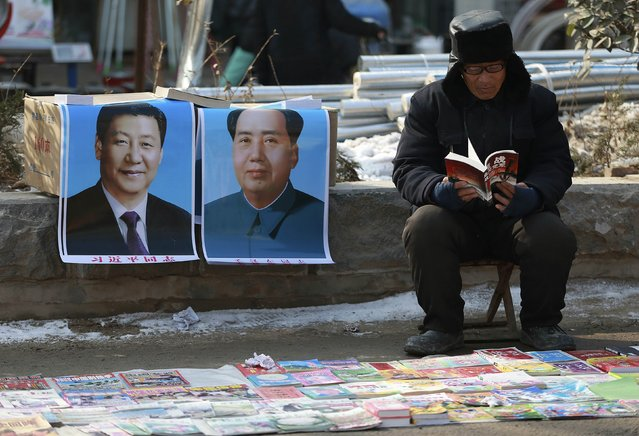 A book vendor reads a book as he waits for customer next to portraits of Chinese President Xi Jinping (L) and late Chairman Mao Zedong, at an open-air fair in Juancheng county, Shandong province January 30, 2015. (Photo by Reuters/Stringer)