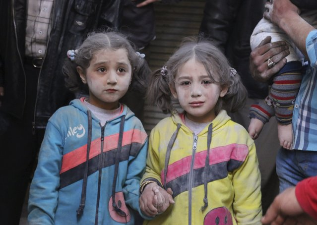 Girls who survived what activists said was a ground-to-ground missile attack by forces of Syria's President Bashar al-Assad, hold hands at Aleppo's Bab al-Hadeed district, Syria April 7, 2015. (Photo by Abdalrhman Ismail/Reuters)