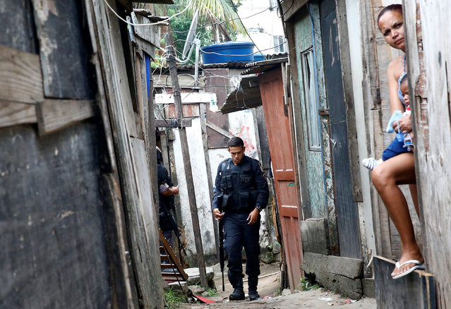 A policeman is pictured near a woman with a baby during an operation against drug dealers in Cidade de Deus or City of God slum in Rio de Janeiro, Brazil, November 23, 2016. (Photo by Ricardo Moraes/Reuters)
