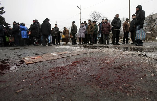 People stand in line to receive humanitarian aid as blood is seen on the ground in front of a delivery point in the Ukrainian forces-controlled town of Debaltseve, Donetsk region February 6, 2015. (Photo by Maxim Shemetov/Reuters)