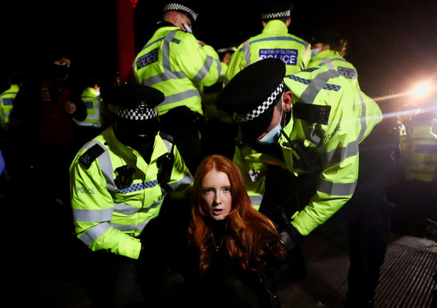 Police detain a woman as people gather at a memorial site in Clapham Common Bandstand, following the kidnap and murder of Sarah Everard, in London, Britain on March 13, 2021. (Photo by Hannah McKay/Reuters)