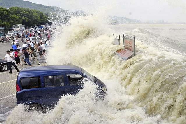 Spectators flee as waves created by a tidal bore crash over a barrier on the Qiantang river at Hangzhou, in east China's Zhejiang province, on August 31, 2011. (Photo by AP Photo via The Atlantic)