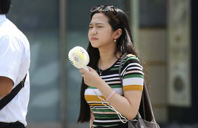 A woman holds a portable fan at a business district in Tokyo, Monday, July 23, 2018. Searing hot temperatures are forecast for wide swaths of Japan and South Korea in a long-running heat wave. The mercury is expected to reach 39 degrees Celsius (102 degrees Fahrenheit) on Monday in the city of Nagoya in central Japan and reach 37 in Tokyo. Deaths have been reported almost every day. (Photo by Koji Sasahara/AP Photo)