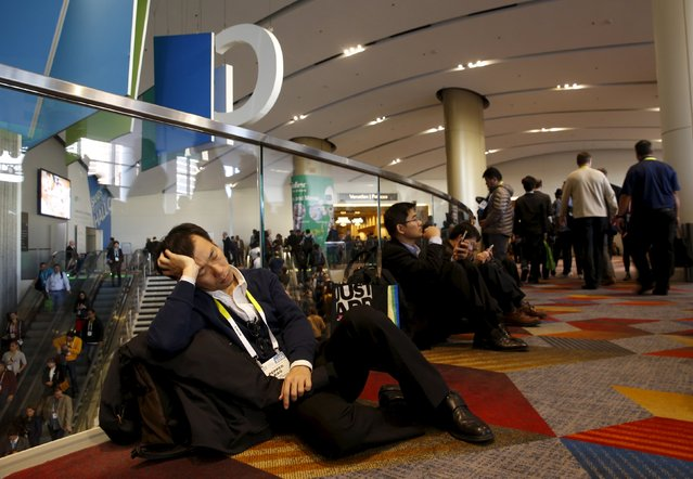 An exhausted attendee takes a nap on the floor during the 2016 CES trade show in Las Vegas, Nevada January 8, 2016. (Photo by Steve Marcus/Reuters)