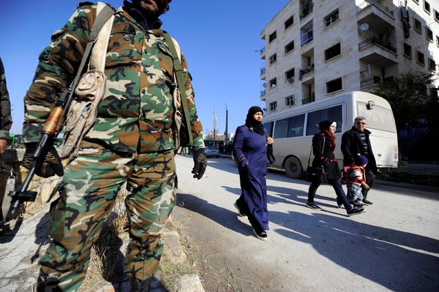 People that came back to inspect their homes walk near goverment soldiers in goverment controlled Hanono housing district in Aleppo, Syria December 4, 2016. (Photo by Omar Sanadiki/Reuters)