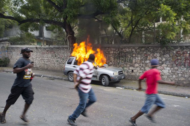 Demosntrators run past a burning car during a street protest after it was announced that the runoff Jan. 24, presidential election had been postponed, in Port-au-Prince, Haiti, Friday, January 22, 2016. (Photo by Dieu Nalio Chery/AP Photo)