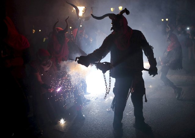 "A reveller dressed as a devil holds a stick with fireworks during traditional ""Correfocs"" (fire runs) to mark the end of the local festivities in Palma, on the Spain's Balearic Island of Mallorca,  January 23, 2016. (Photo by Enrique Calvo/Reuters)"