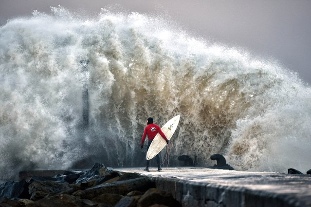 A huge wave crashes against Castlerock pier as professional surfer Al Mennie waits on a break in the swell on December 22, 2016 in Coleraine, Northern Ireland. Storm Barbara is expected to cause major travel disruption when it hits northern parts of the UK later with 90mph winds predicted. The Met Office has issued an amber warning with the worst effects of the storm expected on Friday and Saturday. (Photo by Charles McQuillan/Getty Images)