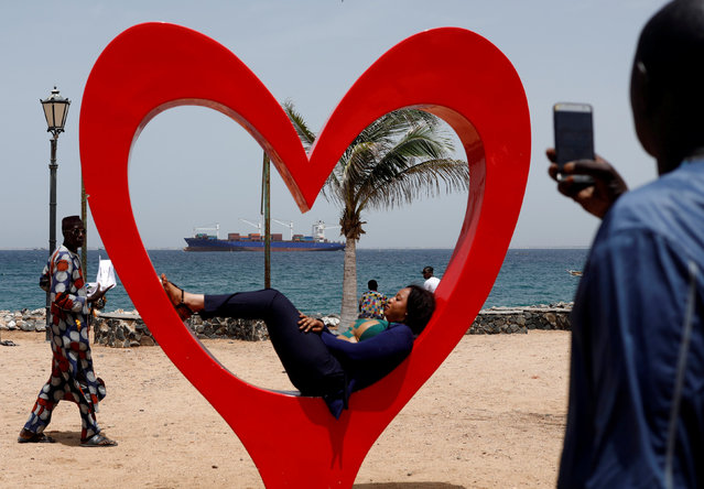 A container ship is seen offshore as a Senegalese woman poses for photograph in the island of Goree off the coast of Dakar, Senegal September 23, 2018. (Photo by Zohra Bensemra/Reuters)