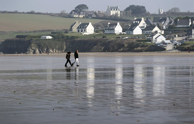 People cross the wet sand during a record low tide on Kerlaz beach near Douarnenez in western France, March 21, 2015. (Photo by Mal Langsdon/Reuters)