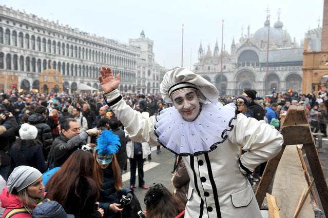A mask salutes in St. Mark's Square on the occasion of the Venice Carnival, in Venice, Italy, Saturday, January 30, 2016. People attended the Venice Carnival, celebrated Saturday under heightened security following the sexual assaults on New Year's Eve in Cologne and the ongoing terror threat in Europe. Authorities have increased surveillance throughout the city, including the number of officers on patrol, both under-cover and in uniform. (Photo by Luigi Costantini/AP Photo)