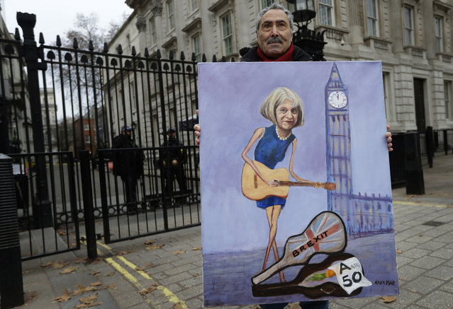 Artist Kaya Mar displays his painting of Theresa May in front of Downing Street in London, Tuesday, December 4, 2018. Britain's Prime Minister Theresa May is due to address Parliament Tuesday, opening five days of debate before a Dec. 11 vote on the divorce agreement. (Photo by Kirsty Wigglesworth/AP Photo)