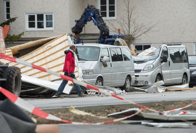 "A man passes damaged vehicles after strong wings have blow parts of a roof from a building in Weilheim, southern Germany, Tuesday, March 31, 2015. Wide parts of Germany were hit by storm ""Niklas"" that caused severe damages. (Photo by Peter Kneffel/AP Photo/DPA)"