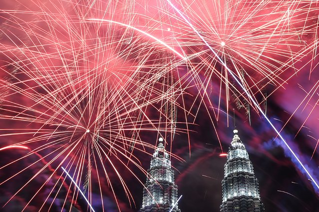 Fireworks illuminate the sky near Malaysia's Petronas Twin Towers during New Year celebrations in Kuala Lumpur on January 1, 2017. (Photo by Mohd Rasfan/AFP Photo)