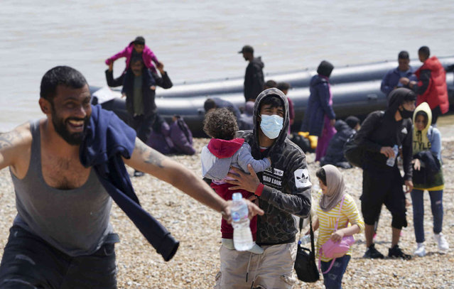 People thought to be migrants make their way up the beach after arriving on a small boat at Dungeness in Kent, England, Monday,  July 19, 2021. They were later taken away by Border Force staff. (Photo by Gareth Fuller/PA Wire via AP Photo)