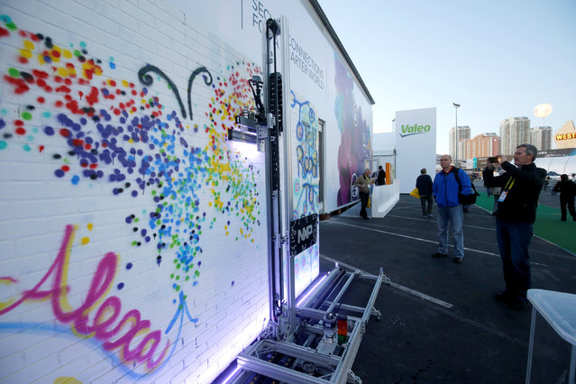 A robotic spray paint artist paints a wall outside the A view of the NXP Semiconductors booth during the 2017 CES in Las Vegas, Nevada January 6, 2017. (Photo by Steve Marcus/Reuters)