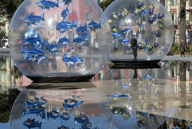 """A man installs fish-shaped balloons in a water fountain to mark April Fools' Day, called """"Poisson d'Avril"""" in France, in the centre of Nice, April 1, 2015. (Photo by Eric Gaillard/Reuters)"""