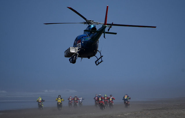 A helicopter flies over competitors riding during Stage 5 of the Dakar 2019 between Tacna and Arequipa on January 11, 2019. (Photo by Franck Fife/AFP Photo)