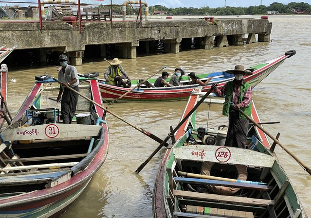 Boatmen wearing face masks wait for passengers at the jetty in Yangon, Myanmar, Thursday, July 8, 2021. (Photo by AP Photo/Stringer)